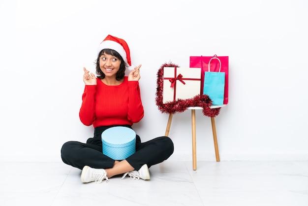 Jovem garota comemorando o natal sentada no chão, isolada em um fundo branco, cruzando os dedos