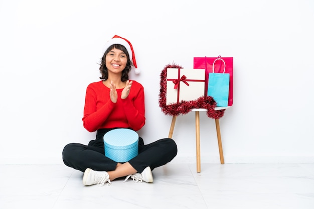 Jovem garota comemorando o natal sentada no chão, isolada no fundo branco, aplaudindo após a apresentação em uma conferência