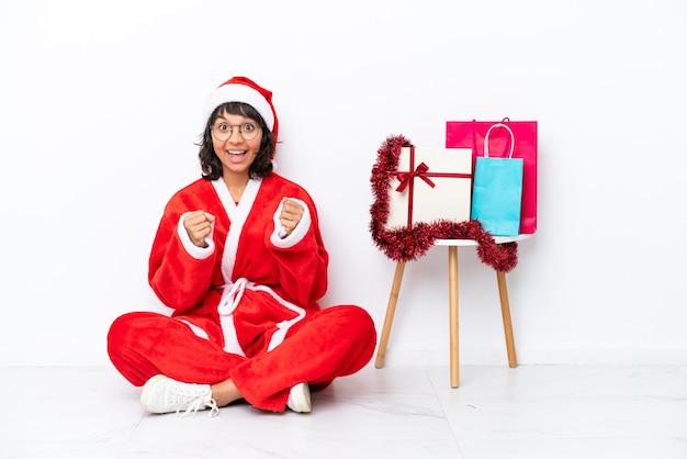 Jovem garota comemorando o natal sentada no chão, isolada no fundo branco, comemorando a vitória na posição vencedora
