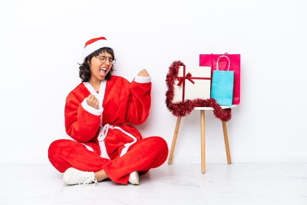 Jovem garota comemorando o natal sentada no chão, isolada no fundo branco, comemorando uma vitória