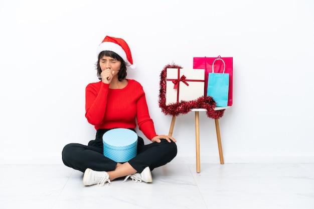 Jovem garota comemorando o natal sentada no chão, isolada no fundo branco, está sofrendo de tosse e se sentindo mal