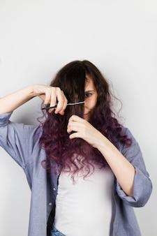 Jovem garota corta para si mesma cabelo roxo encaracolado
