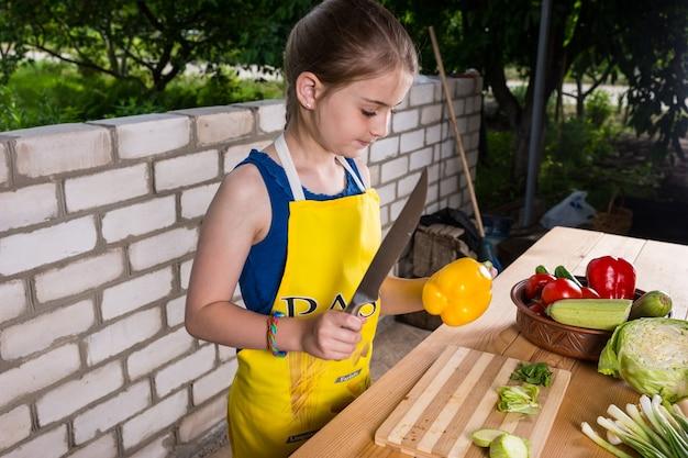 Jovem garota cortando legumes em uma mesa de madeira ao ar livre, segurando uma grande faca de cozinha na mão enquanto se prepara para cortar um pimentão