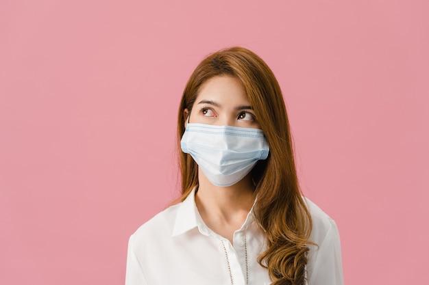 Jovem garota da ásia usando máscara médica com vestido de pano casual e olhando para o espaço em branco, isolado no fundo rosa.