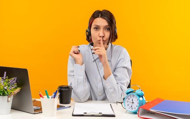 Jovem garota da central de atendimento usando fone de ouvido, sentada na mesa com ferramentas de trabalho, gesticulando silêncio, olhando para a câmera isolada em fundo laranja