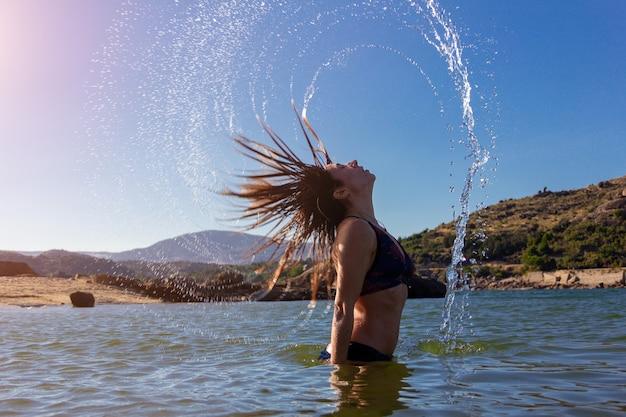 Jovem garota de biquíni fazendo uma onda com o cabelo em um lago conceito de movimento de verão espaço de cópia