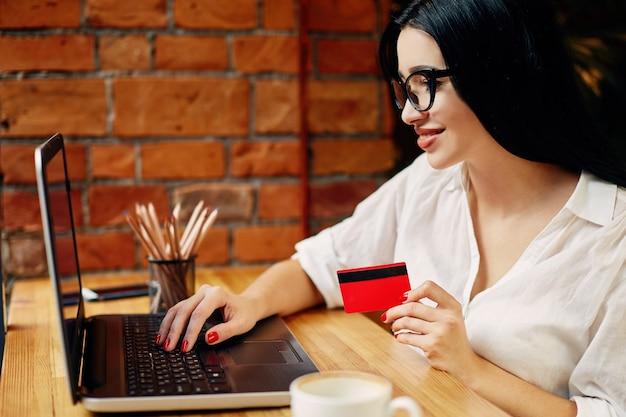 Jovem garota de cabelo preto, usando óculos, sentada no café com laptop, telefone celular, cartão de crédito e uma xícara de café, conceito freelance, compras online, camisa branca.