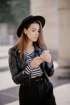 Jovem garota de cabelos castanhos em uma jaqueta de couro, chapéu preto no calçadão da cidade e joga no celular