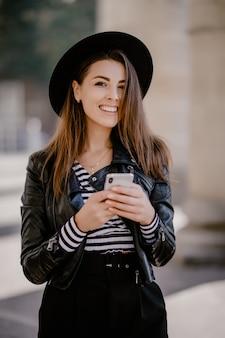 Jovem garota de cabelos castanhos em uma jaqueta de couro e chapéu preto no calçadão da cidade posando com um telefone celular