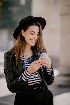 Jovem garota de cabelos castanhos em uma jaqueta de couro e chapéu preto no calçadão da cidade