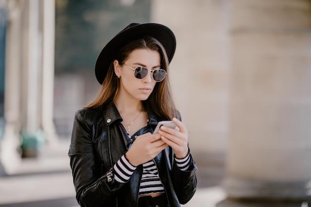 Jovem garota de cabelos castanhos em uma jaqueta de couro e óculos, chapéu preto no calçadão da cidade