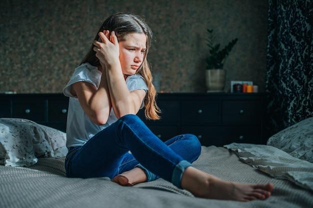 Jovem garota de cabelos escuros se agarra à orelha dolorida com as mãos. uma garota de blusa branca e calça jeans está sentada em uma cama no quarto dela.