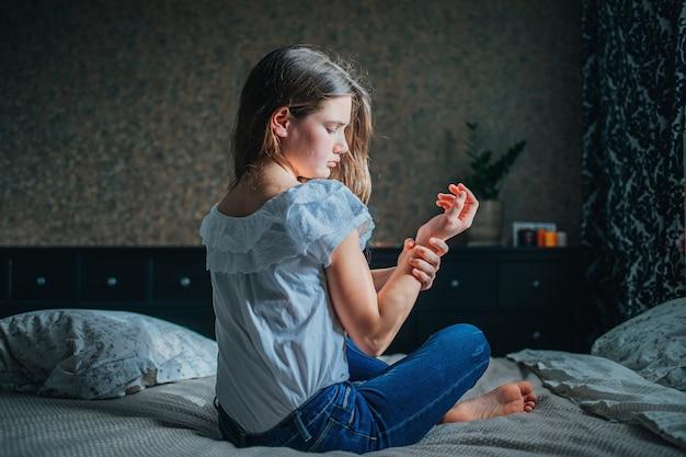 Jovem garota de cabelos escuros se agarra ao pulso dolorido enquanto está sentada na cama em seu quarto.