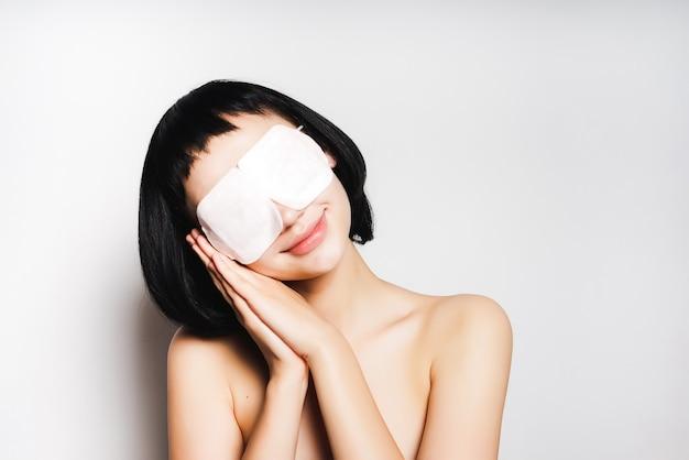 Jovem garota de cabelos negros mostra que está dormindo com uma máscara, sorrindo. isolado em um fundo cinza