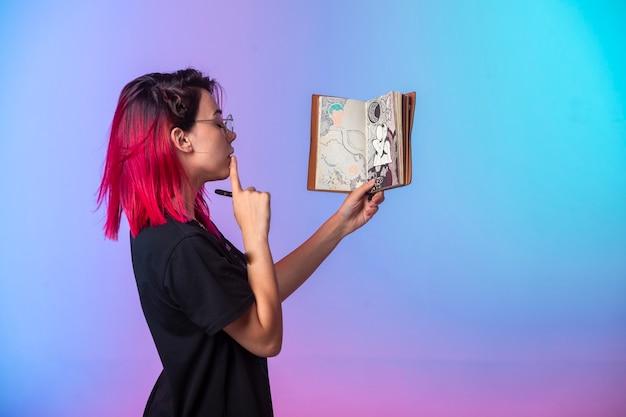 Jovem garota de cabelos rosa segurando um caderno e olhando para.