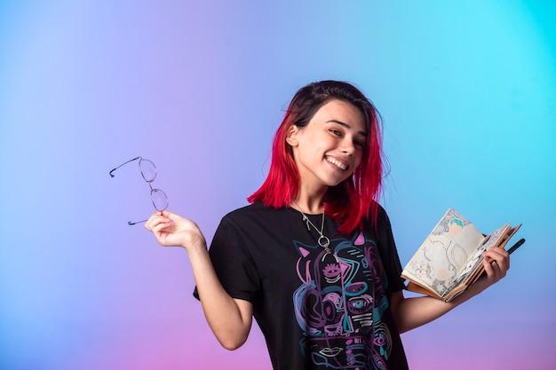 Jovem garota de cabelos rosa segurando um caderno e se sentindo positiva.