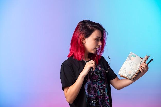Jovem garota de cabelos rosa segurando um caderno.