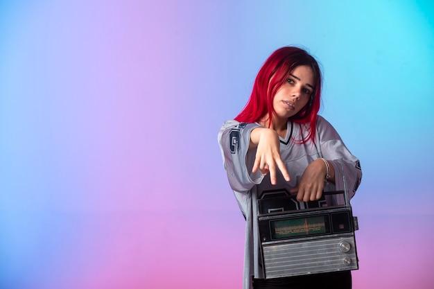 Jovem garota de cabelos rosa segurando um rádio vintage.