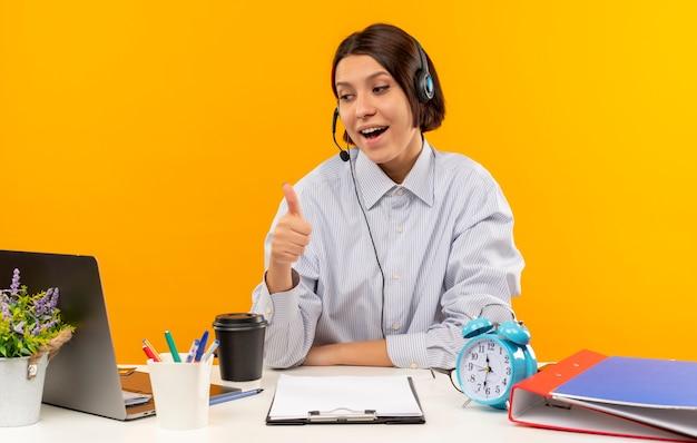Jovem garota de call center impressionada usando fone de ouvido, sentada na mesa, olhando para o laptop mostrando o polegar isolado em laranja