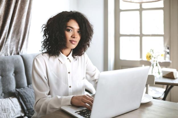 Jovem garota de camisa branca sentado em um restaurante com o laptop. linda garota afro-americana com cabelo escuro e encaracolado trabalhando em seu laptop no café