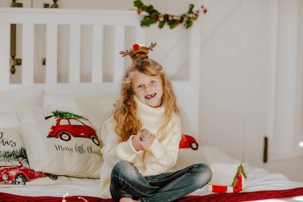 Jovem garota desdentada bonita camisola branca e penteados como veado de natal