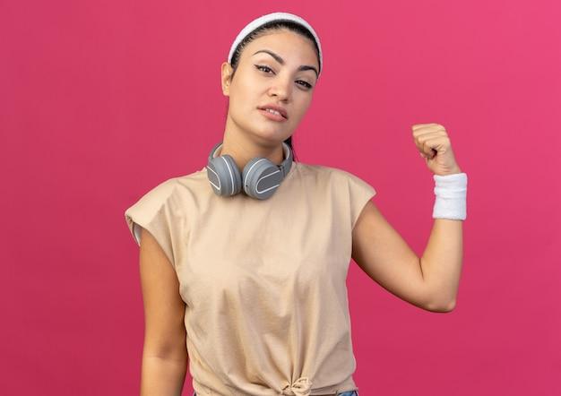 Jovem garota desportiva caucasiana confiante usando fita para a cabeça e pulseiras com fones de ouvido ao redor do pescoço, olhando para a frente, apontando para trás, isolado na parede rosa