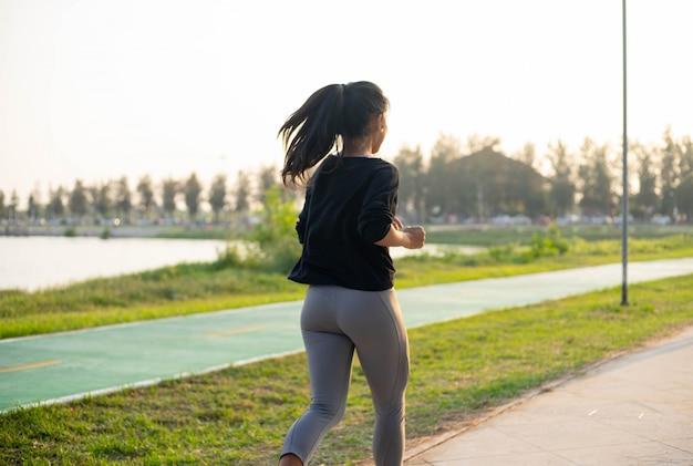 Jovem garota desportiva correndo no parque durante o pôr do sol