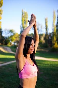 Jovem garota desportiva fazendo yoga no parque