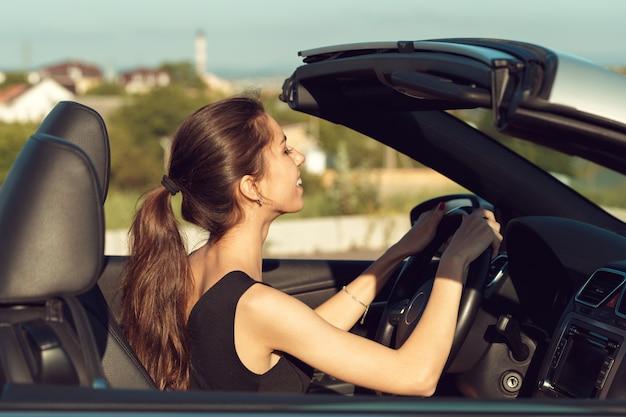 Jovem garota dirigindo carro cabrio, na luz do sol