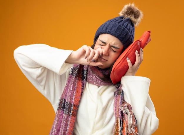 Jovem garota doente caucasiana carrancuda usando um manto de inverno, chapéu e lenço tocando a cabeça com um saco de água quente, limpando o nariz com os olhos fechados, isolado na parede laranja