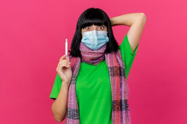 Jovem garota doente caucasiana impressionada usando máscara e lenço segurando o termômetro verticalmente e mantendo a mão atrás da cabeça olhando para a câmera isolada no fundo carmesim com espaço de cópia