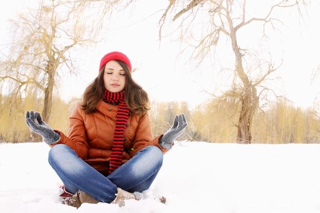 Jovem garota em pose de lótus na neve