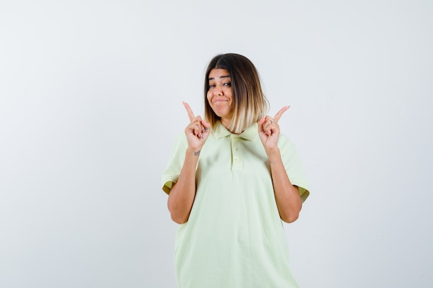 Jovem garota em t-shirt apontando para cima com os dedos indicadores e olhando feliz, vista frontal.