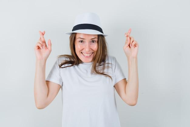 Jovem garota em t-shirt branca, chapéu mantendo os dedos cruzados e olhando alegre, vista frontal.