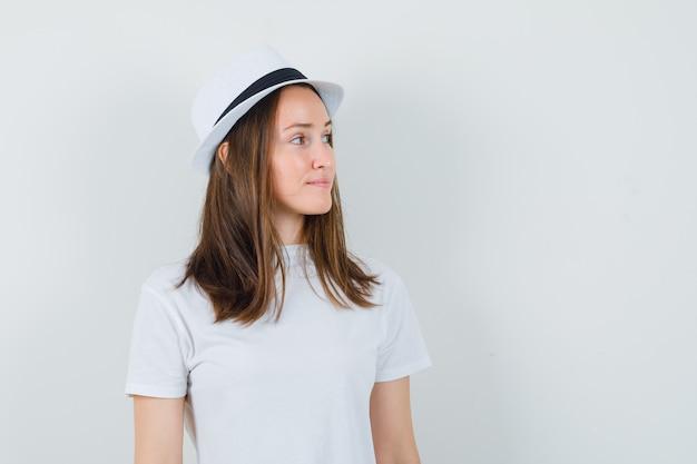Jovem garota em t-shirt branca, chapéu, olhando de lado e olhando graciosa, vista frontal.