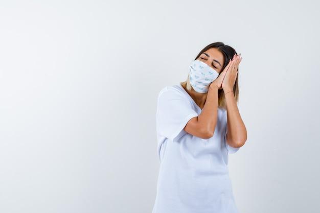 Jovem garota em t-shirt branca e máscara, inclinando a bochecha nas palmas das mãos como travesseiro e parecendo com sono, vista frontal.