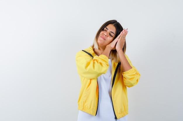 Jovem garota em t-shirt branca, jaqueta amarela, bochecha nas palmas das mãos como travesseiro e parecendo com sono, vista frontal.