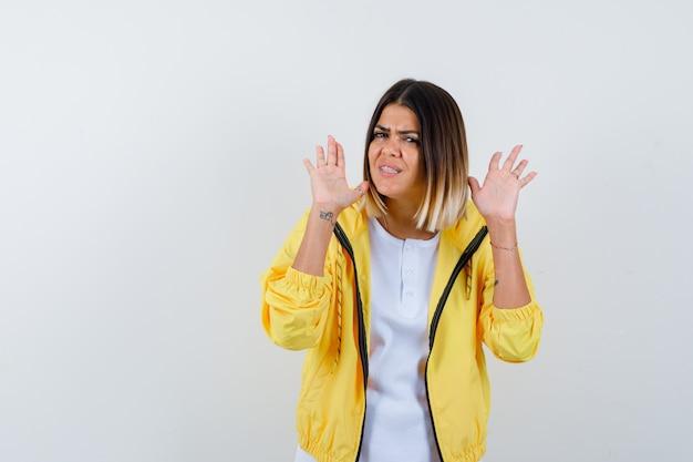 Jovem garota em t-shirt branca, jaqueta amarela, levantando as palmas das mãos em gesto de rendição e olhando com medo, vista frontal.