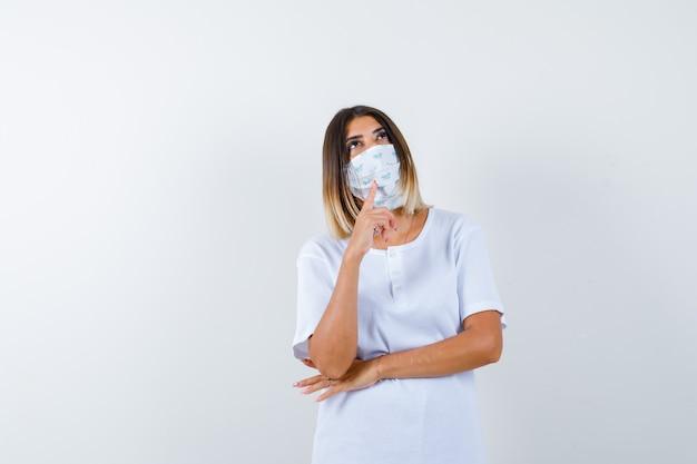 Jovem garota em t-shirt branca, máscara colocando o dedo indicador sob o queixo, olhando para cima, pensando em algo e parecendo pensativo, vista frontal.