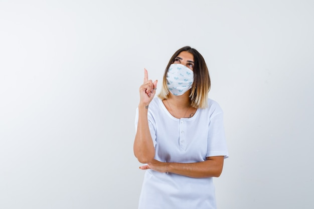 Jovem garota em t-shirt branca, máscara levantando o dedo indicador em gesto de eureka, mantendo a mão sob o cotovelo e parecendo sensível, vista frontal.