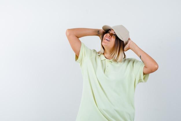 Jovem garota em t-shirt e boné de mãos dadas atrás da cabeça, olhando para longe e olhando feliz, vista frontal.