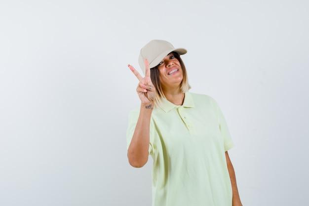 Jovem garota em t-shirt e boné, mostrando o gesto de paz e olhando feliz, vista frontal.