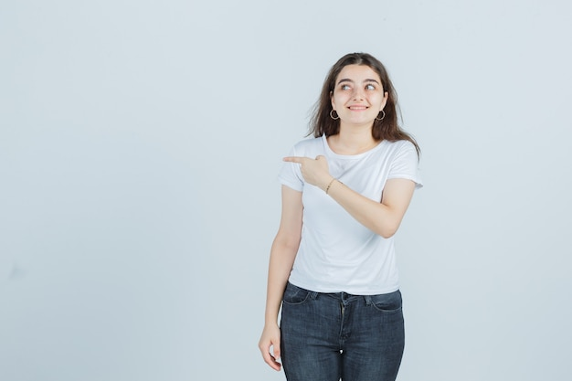 Jovem garota em t-shirt, jeans apontando para o lado, olhando para o lado e parecendo curiosa, vista frontal.