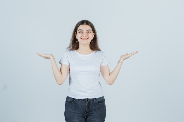 Jovem garota em t-shirt, jeans, espalhando as palmas das mãos para fora e parecendo feliz, vista frontal.