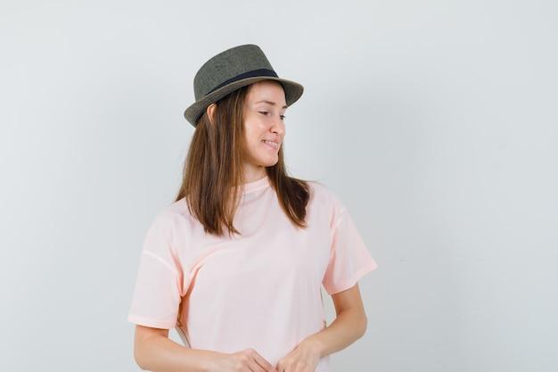 Jovem garota em t-shirt rosa, chapéu olhando para baixo e parecendo um sonho, vista frontal.
