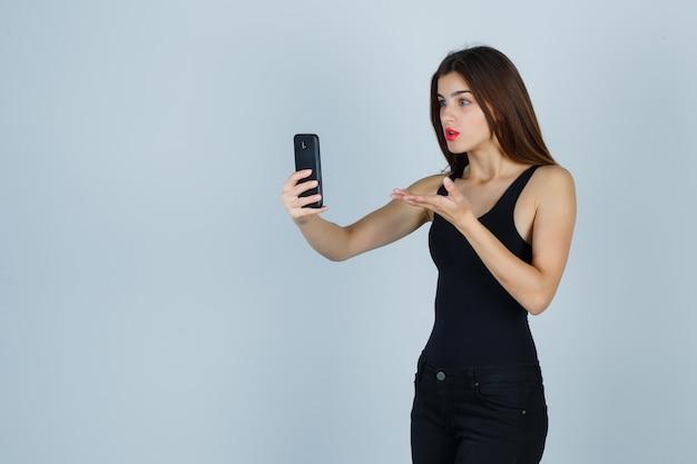 Jovem garota em top preto, calças, falando com alguém através do telefone, esticando a mão de forma questionadora e parecendo surpresa, vista frontal.