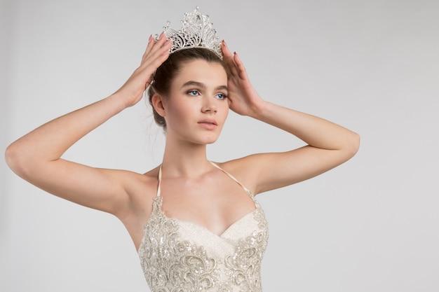 Jovem garota em um lindo vestido, coloca uma coroa na cabeça, um olhar de superioridade e liderança, parece longe, conceito, closeup