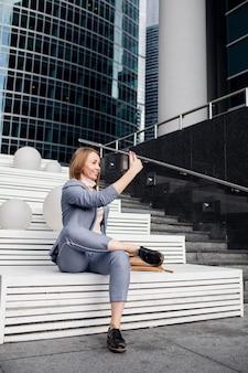 Jovem garota em um terno de negócio tira uma selfie nas escadas.
