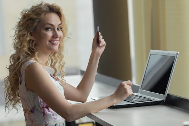 Jovem garota em um vestido com cartão de crédito na mão, sorrindo e olhando para a câmera. conceito de compras online