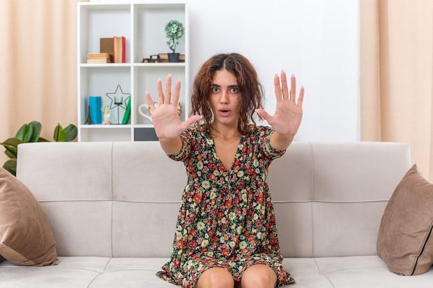 Jovem garota em um vestido floral parecendo preocupada fazendo gesto de parada com as mãos, sentada em um sofá na sala de estar iluminada